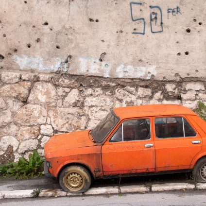 Travel photography, an old orange Yugoslavian car (Zastava) in front of a building with bullet holes