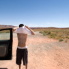 Travel photograph of a man changing his shirt in the middle of nowhere